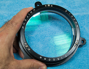 telescope objective lens, after cleaning and illuminated to demonstrated the green multilayer antireflection coatings (82,557 bytes)